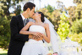 Young newlywed couple kissing besides wedding cake at the park