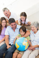 Multigeneration family looking at globe in house