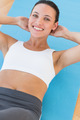 Smiling young woman doing abdominal crunches on exercise mat at a gym