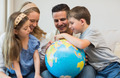 Happy family of four searching places on globe in house