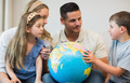 Family with globe looking at boy in house
