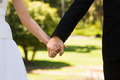 Extreme close-up mid section of a newlywed couple holding hands in the park