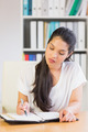 Young businesswoman writing notes in diary at office desk