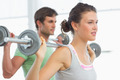 Fit young man and woman lifting barbells in the gym