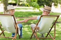 Rear view portrait of a relaxed mature couple sitting in deck chairs at the park
