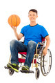 Hopeful young man sitting on a wheelchair with a basketball in studio - PhotoDune Item for Sale