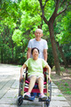 Senior woman sitting on a wheelchair with his husband in the park - PhotoDune Item for Sale