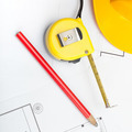 Yellow construction helmet with pencil and measure tape over some documents - 1 to 1 ratio - PhotoDune Item for Sale