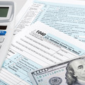 USA Tax Form 1040 with calculator and 100 US dollar bills - PhotoDune Item for Sale