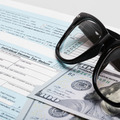 USA 1040 Tax Form with glasses and two 100 US dollar bills - PhotoDune Item for Sale