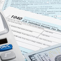 US Tax Form 1040 with calculator and 100 US dollar bills - PhotoDune Item for Sale