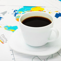 Coffee cup over world map and financial documents - 1 to 1 ratio - PhotoDune Item for Sale
