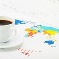 White coffee cup over world map and financial documents - studio shot - 1 to 1 ratio - PhotoDune Item for Sale