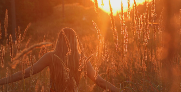 Girl Walking in a Field at Sunset