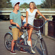 Happy couple riding a bicycle in the city street - PhotoDune Item for Sale