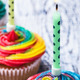 burning candle on colorful cupcakes with cream - PhotoDune Item for Sale