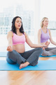 Meditating pregnant women in yoga class in lotus pose in a fitness studio