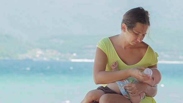 Mother Feeding Baby Boy With Bottle on the Beach