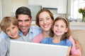 Closeup portrait of smiling family with laptop in house