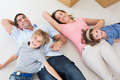 Portrait of happy family lying on floor in their new house