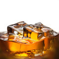 Splash of whiskey with ice in glass isolated on white - PhotoDune Item for Sale