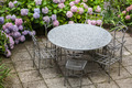 table and chairs in garden with color hydrangea - PhotoDune Item for Sale
