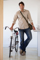 Casual businessman standing with his bike smiling at camera in the office
