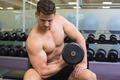 Shirtless bodybuilder lifting heavy black dumbbell at the gym