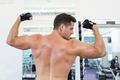 Shirtless bodybuilder flexing his biceps at the gym
