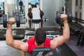 Bodybuilder lying on bench lifting heavy dumbbells at the gym