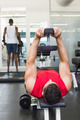 Bodybuilder lying on bench lifting heavy dumbbell at the gym
