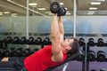 Bodybuilder lying on bench lifting dumbbells at the gym