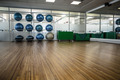 Large empty fitness studio with shelf of exercise balls at the leisure center