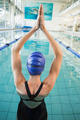 Fit swimmer in the pool with arms raised at the leisure center