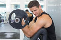 Focused bodybuilder lifting heavy black dumbbell at the gym