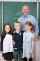 Elderly male teacher with three young students - PhotoDune Item for Sale