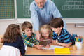 Smiling young children using a tablet in class - PhotoDune Item for Sale