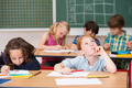 Young girl sitting thinking in class at school - PhotoDune Item for Sale