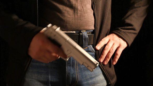 Man Holding A Gun Reloads It