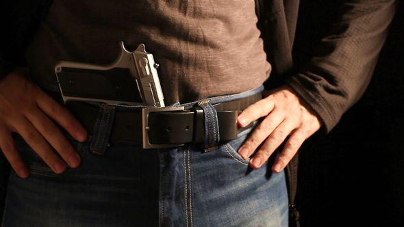Man Reloads The Gun And Puts It In His Belt
