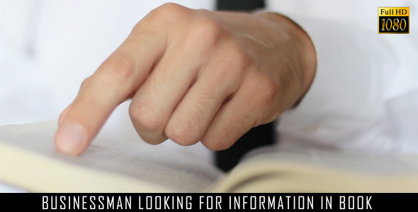 Businessman Looking For Information In Book