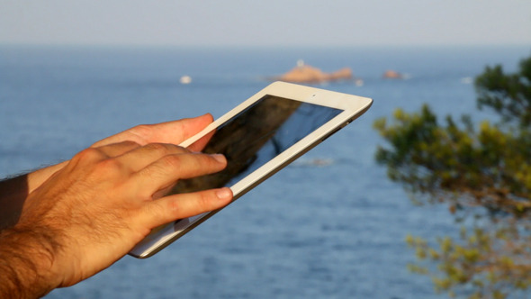 Browsing Tablet Next to the Seashore