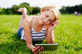 Blond woman browsing websites on her tablet while in the green - PhotoDune Item for Sale