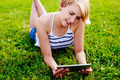 Blond young lady surfing the web and lying on the grass - PhotoDune Item for Sale