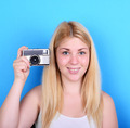 Portrait of young female holding vintage camera against blue bac - PhotoDune Item for Sale