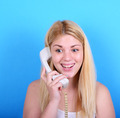 Portrait of young woman talking on retro phone against blue back - PhotoDune Item for Sale