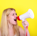 Portrait of young woman shouting with a megaphone against yellow - PhotoDune Item for Sale