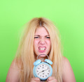 Portrait of sleepy young female in chaos holding clock against g - PhotoDune Item for Sale