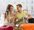 Couple with luggage reading map - PhotoDune Item for Sale