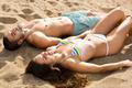 couple sunbathing on the sand - PhotoDune Item for Sale